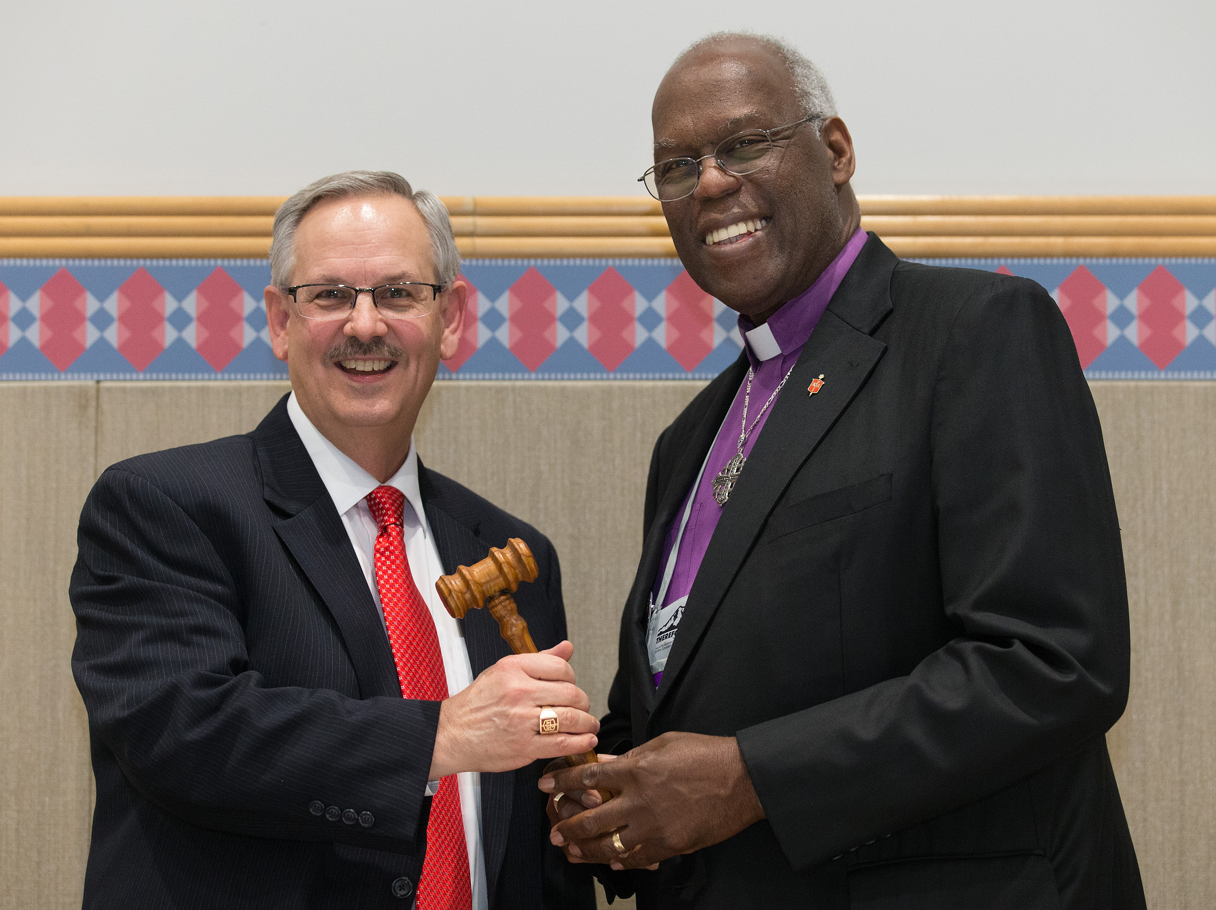 Bishop Bruce R. Ough (left) receives the gavel as incoming president of the United Methodist Council of Bishops from outgoing president Warner H. Brown, Jr. during the 2016 General Conference in Portland, Ore. Photo by Mike DuBose, UMNS