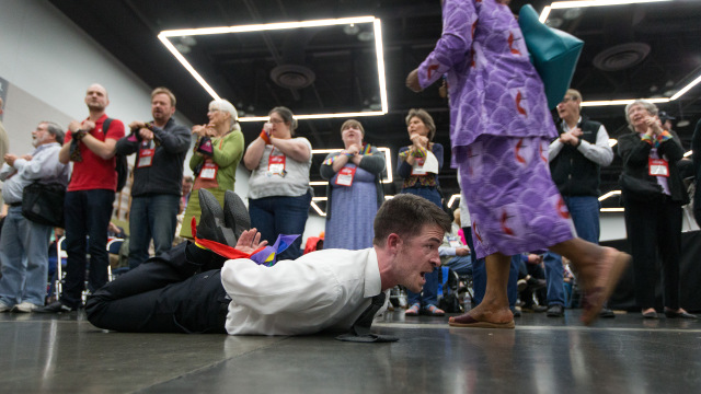 The Rev. Will Green lies on the floor of the 2016 United Methodist General Conference in Portland, Ore., with his hands and feet bound to protest the denomination's policies on human sexuality. Delegates returning from their lunch break passed by protestors on the floor and lining the entryway to the meeting area. Photo by Mike DuBose, UMNS
